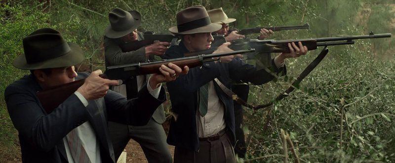 Four men firing rifles