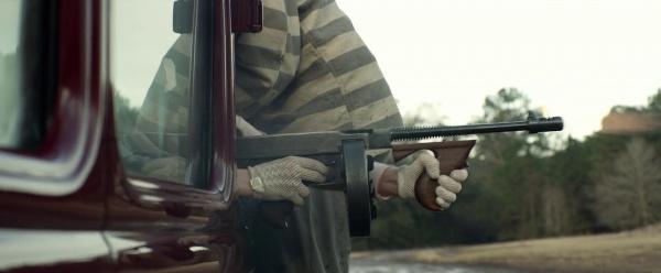 Woman firing a gun from a car