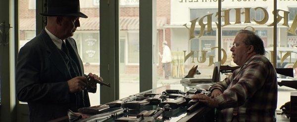 Kevin Costner looking at a revolver